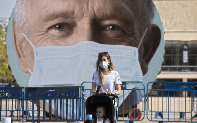 A woman walks past a banner encouraging people to wear face masks in Tel Aviv, Israel, Sept. 24, 2020. (AP/Sebastian Scheiner)