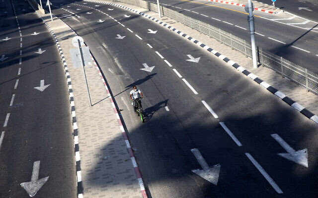 A man rides his bicycle on a slow traffic road following restrictions in the  nationwide lockdown, in Tel Aviv, Israel, Sept 25, 2020. (AP Photo/Oded Balilty)