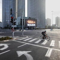 A man rides a bicycle next to a billboard calling people to wear masks, on empty road following new restrictions in the three-week nationwide lockdown, in Tel Aviv, Israel, Sept. 26, 2020. (AP Photo/Oded Balilty)
