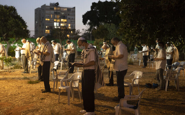 Israelis pray outside a synagogue ahead of Yom Kippur, the holiest day in the Jewish year in Tel Aviv, Israel,  Sept. 27, 2020. (AP Photo/Sebastian Scheiner)