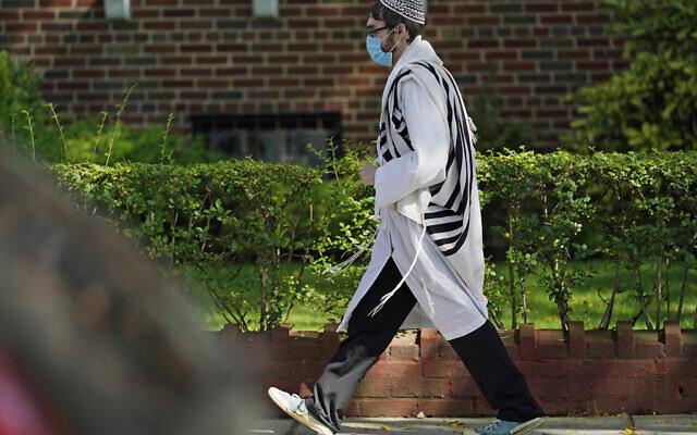 A Jewish man  walks through the Midwood neighborhood of Brooklyn, Monday, Sept. 28, 2020, in New York (AP Photo/Kathy Willens)