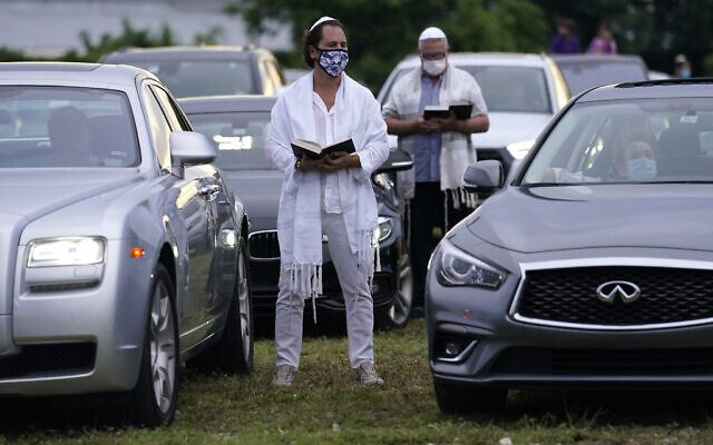 Illustrative: Congregants stand outside their vehicles during a Yom Kippur service hosted by the Aventura Turnberry Jewish Center, during the coronavirus pandemic, September 28, 2020, at the Dezerland Park drive-in theatre in North Miami, Florida. (AP Photo/Lynne Sladky)