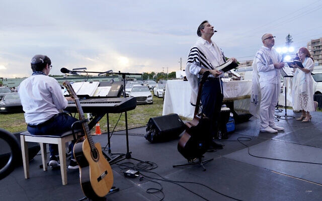 Rabbi Jonathan Berkun, center, leads a Yom Kippur service hosted by the Aventura Turnberry Jewish Center as people watch from their vehicles, during the coronavirus pandemic, Sept. 28, 2020, at the Dezerland Park drive-in theatre in North Miami, Florida. (AP Photo/Lynne Sladky)