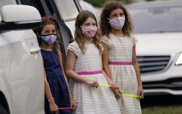 Ariela Klepacz, left, Sarah Halpern, center, and Gabriela Klepacz, right, stand outside of their vehicle during a Yom Kippur service hosted by the Aventura Turnberry Jewish Center, during the coronavirus pandemic, Sept. 28, 2020, at the Dezerland Park drive-in theatre in North Miami, Florida (AP Photo/Lynne Sladky)