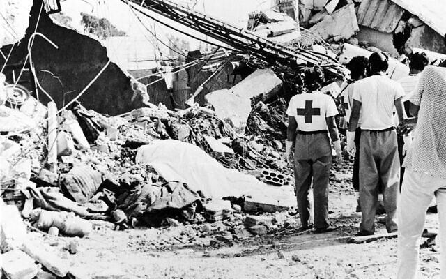 Red Cross workers looking at a body, covered with a blanket, shortly after bulldozers started cleaning up the area in Sabra Lebanese refugee camp, on September 20, 1982. (AP Photo/Nash)