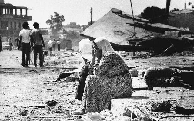 Two Palestinian women weep as they sit on the curb in the Sabra Palestinian refugee camp in West Beirut, Lebanon, September 19, 1982, after they found bodies of relatives. (AP Photo/Bill Foley)