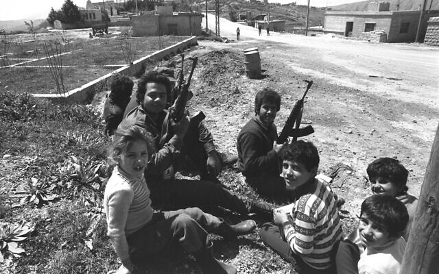 Illustrative: Children sit with Phalangist soldiers at Klea, a Maronite village in southern Lebanon, April 1, 1978. (Israeli GPO/ Moshe Milner)