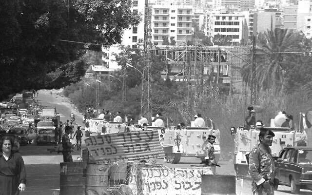 Illustrative: Italian armored personnel carriers drive through the Sam'an Gallery passage in East Beirut, which is guarded by Lebanese soldiers but still bears the Hebrew signage commanding drivers, 'Stop, border ahead,' August 26, 1982. (Israeli GPO/ Dalia Yankovitz)