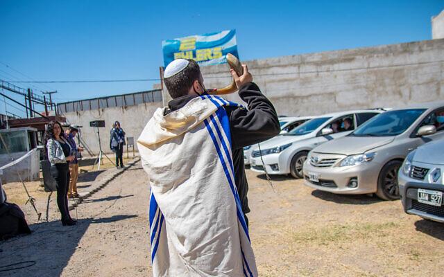 "Rabbi Marcelo Polakoff, chief rabbi of the Israelite Union Center of Cordoba, blows a shofar at a ""drive-in"" Rosh Hashanah service, September 20, 2020. (Courtesy of Israelite Union Center of Cordoba/via JTA)"