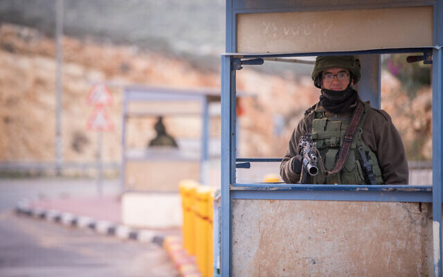 Israeli soldiers guard at a bus stop near the settlement of Kokhav HaShahar, in the West Bank, on January 6, 2019. (Yonatan Sindel/Flash90)