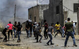 Palestinians clash with Israeli soldiers during a protest against Israel's plan to annex parts of the West Bank, in the village of Kfar Qaddum, near the West Bank city of Nablus on June 19, 2020. (Nasser Ishtayeh/Flash90)