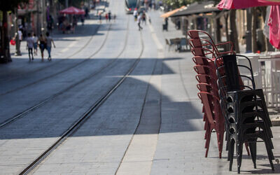 Stacked chairs outside a restaurant on Jaffa Street in Jerusalem on July 17, 2020. (Yonatan Sindel/Flash90)