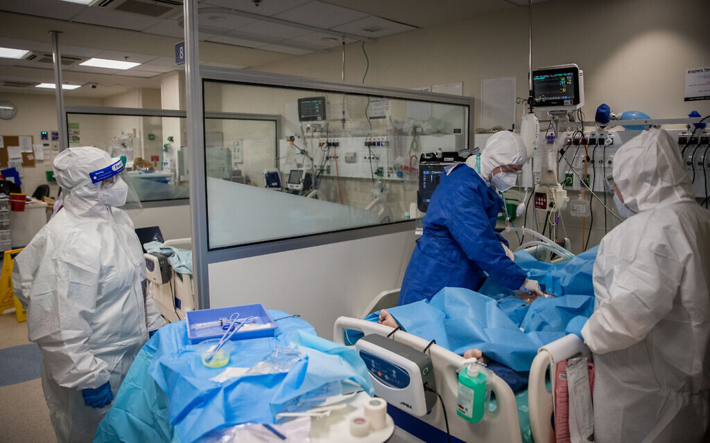 Medical staff wearing protective clothes as they work at the coronavirus ward of Shamir Medical Center (Assaf Harofeh), in Be'er Ya'akov, southeast of Tel Aviv, August 20, 2020.(Yonatan Sindel/Flash90)
