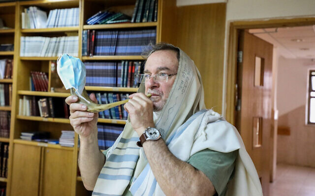 Illustrative: A man blows a shofar covered with a face mask at a synagogue in the West Bank settlement of Efrat on August 21, 2020. (Gershon Elinson/Flash90)