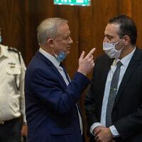Minister of Defense Benny Gantz speaks with Likud parliament member Miki Zohar during a vote at the Knesset, on August 24, 2020. (Oren Ben Hakoon/POOL vis Flash 90)