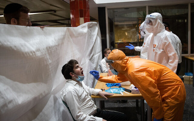 Illustrative: United Hatzalah workers wearing protective clothing as a preventive measure against the coronavirus test ultra-Orthodox Jewish men, at the Wolfson Yeshiva in Jerusalem on August 27, 2020. (Yonatan Sindel/Flash90)