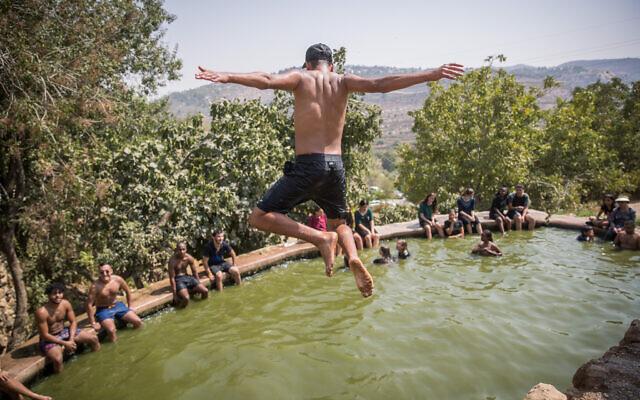 People enjoy a hot summer day at the Ein Lavan Spring in the Jerusalem Mountains, August 30, 2020. (Yonatan Sindel/Flash90)