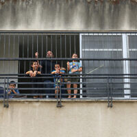 A father seen with his kids at home after the cabinet voted not to open schools in hot zones, in the northern Israeli city of Tiberias, September 1, 2020. (David Cohen/Flash90)
