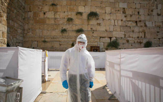 An Orthodox Jewish talmudic seminary student wearing protectives suit, gloves, face mask and a face shield prays at the Western Wall in the Old City of Jerusalem, September 3, 2020. (Olivier Fitoussil/Flash90)