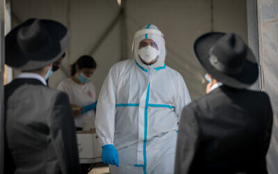 Magen David Adom medical workers test Israelis at a drive-through site to collect samples for coronavirus testing in Jerusalem on September 8, 2020. (Yonatan Sindel/Flash90)