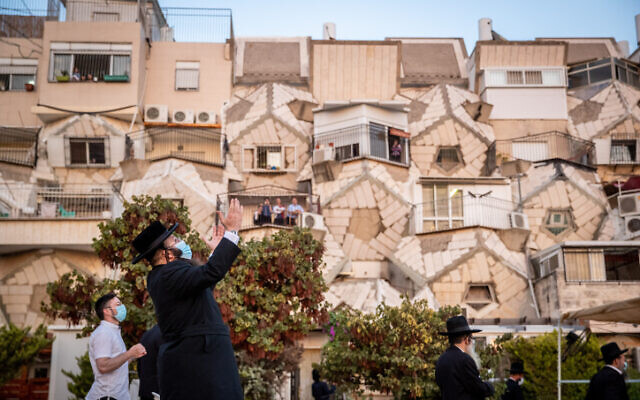 Ultra orthodox Jewish men pray outside an apartment building in the neighborhood of Ramot, in Jerusalem on September 9, 2020. (Yonatan Sindel/Flash90)