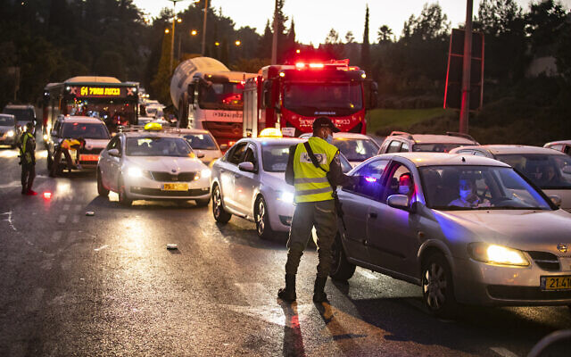 Israeli police at the entrance to the Jerusalem neighborhood of Ramot enforce a nightly curfew aimed at containing the coronavirus, September 13, 2020. (Yonatan Sindel/Flash90)