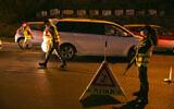 Police officers enforce an overnight curfew at the entrance to the Jerusalem neighborhood of Ramot on September 13, 2020. (Yonatan Sindel/Flash90)