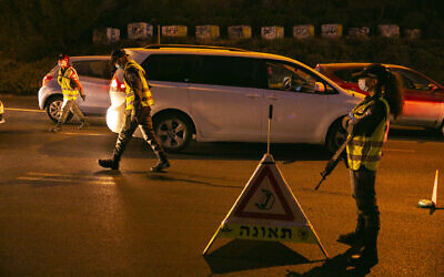 Police officers enforce an overnight curfew at the entrance to the Jerusalem neighborhood of Ramot on September 13, 2020. (Yonatan Sindel/Flash90)