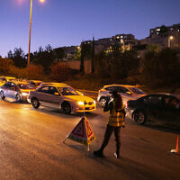 Police seen at the entrance to the  Ramot neighborhood of Jerusalem as Israel enforces a night curfew, applied to some 40 cities and areas all over Israel which have been badly affected by the coronavirus, September 13, 2020. (Yonatan Sindel/Flash90)
