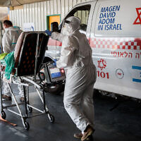 Magen David Adom workers wearing protective clothing outside the coronavirus unit at Shaare Zedek hospital in Jerusalem on September 14, 2020 (Nati Shohat/Flash90)