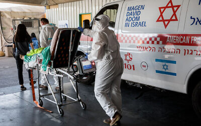 Magen David Adom workers wearing protective clothing outside the coronavirus unit at Shaare Zedek hospital in Jerusalem, September 14, 2020 (Nati Shohat/Flash90)
