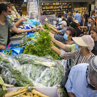Israelis, wearing face masks for fear of the coronavirus, shop for groceries at the Mahane Yehuda market in Jerusalem on September 14, 2020. (Olivier Fitoussi/Flash90)