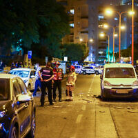 Police and medical personnel at the scene where a rocket fired from the Gaza Strip hit a road in the southern city of Ashdod on September 15, 2020 (Flash90)