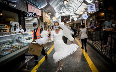 An Israeli bride with a face mask walks at the Mahane Yehuda Market in Jerusalem on September 15, 2020. (Yonatan Sindel/Flash90)