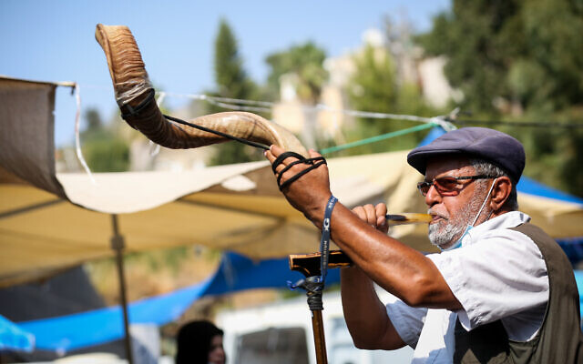 An Israeli man blows a shofar at the market in the northern city of Safed on September 16, 2020. (David Cohen/Flash90)