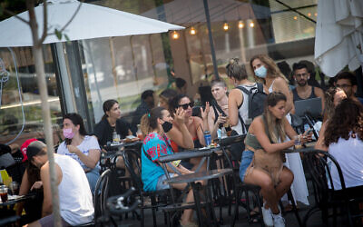 People sit at a cafe in Tel Aviv, September 16, 2020. (Miriam Alster/FLASH90)