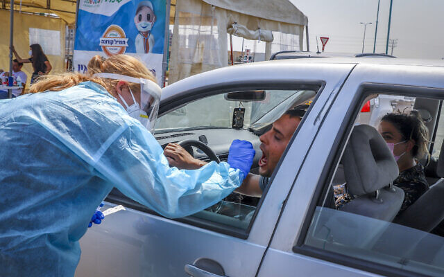 A Clalit healthcare worker takes a swab sample at drive-through coronavirus testing site in the central city of Lod, on September 17, 2020. (Yossi Aloni/Flash90)