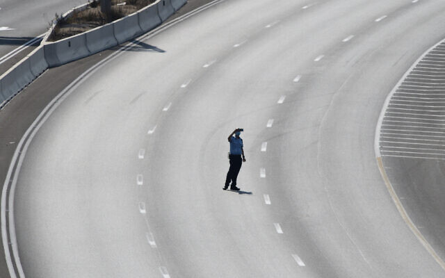 An Israeli Policemen is taking a picture with his cell phone while standing at the middle of Highway 1, leading to Jerusalen, as a country-wide lockdown becomes effective ahead of the Jewish New Year Eve on Sep. 18, 2020. (Gili Yaari / Flash90 )