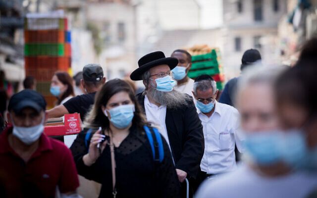 People wearing face masks shop at the Mahane Yehuda Market in Jerusalem on September 18, 2020 (Yonatan Sindel/Flash90)
