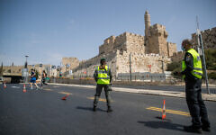 Police at a temporary checkpoint on a nearly empty road outside Jerusalem's Old City on September 19, 2020, during a nationwide coronavirus lockdown. (Yonatan Sindel/Flash90)