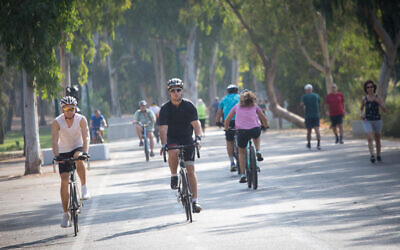 Bicylcists ride their bikes in a park in Tel Aviv, on September 20, 2020 (Miriam Alster/Flash90)
