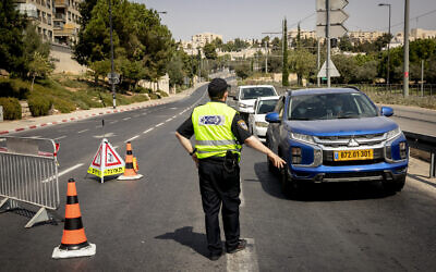 A police officer stops cars at a checkpoint in Jerusalem on September 20, 2020, amid a nationwide coronavirus lockdown. (Olivier Fitoussi/Flash90)