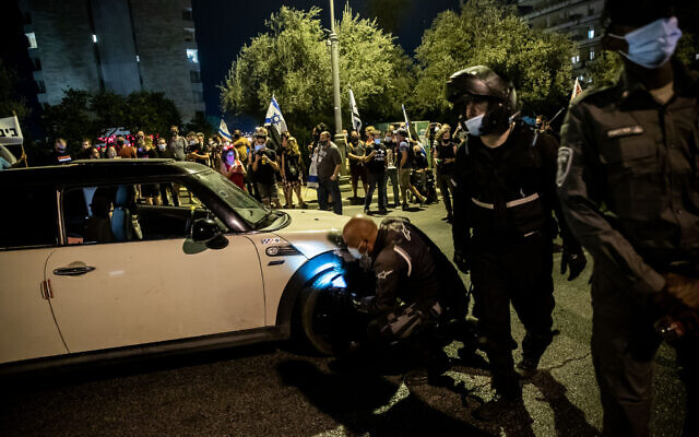 Police officers search the car of a man who sped toward police and demonstrators during a protest against Prime Minister Benjamin Netanyahu, outside his official residence in Jerusalem on September 20, 2020. (Yonatan Sindel/Flash90)