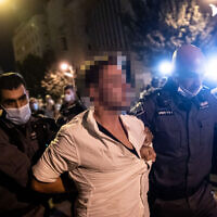 Police arrest a man suspected of speeding in his car toward protesters during a rally against Prime Minister Benjamin Netanyahu outside his official residence in Jerusalem, September 20, 2020. (Yonatan Sindel/Flash90)