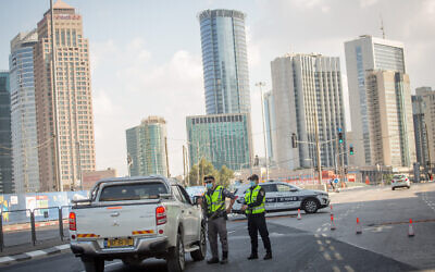 Police set up a temporary roadblock on Menachem Begin Street in Tel Aviv to enforce a coronavirus lockdown, on September 23, 2020. (Miriam Alster/Flash90)