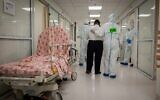 Hospital team members wearing protective clothes as they work at the Coronavirus ward of Shaare Zedek hospital in Jerusalem on September 23, 2020 (Nati Shohat/Flash90)