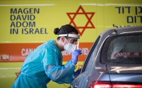A medical team member wearing protective gear takes a swab from a woman to test for COVID-19, outside the coronavirus unit at Shaare Zedek hospital in Jerusalem on September 24, 2020. (Yonatan Sindel/Flash90)