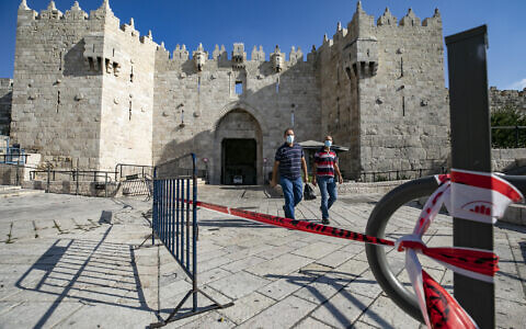 People walk outside the Damascus Gate to the Old City of Jerusalem on September 25, 2020, amid a nationwide coronavirus lockdown. (Olivier Fitoussi/Flash90)