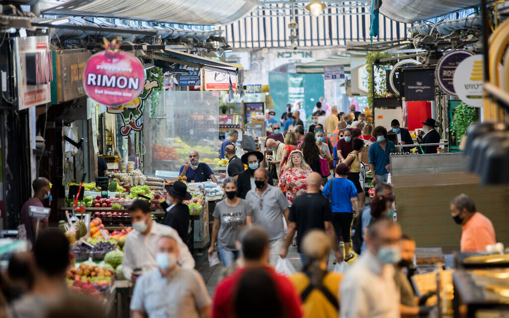 People, some of them wearing face masks, shop at the Mahane Yehuda Market in Jerusalem on September 25, 2020, during a nationwide lockdown to prevent the spread of COVID-19. (Yonatan Sindel/Flash90)