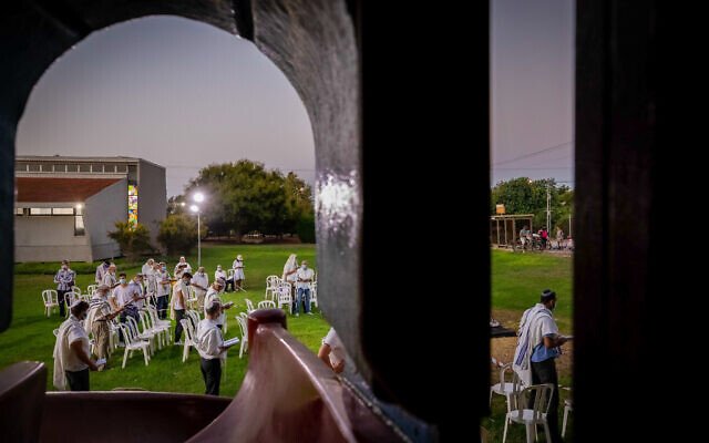 Jewish men pray at the end of Yom Kippur, the Day of Atonement, and the holiest of Jewish holidays, at a public space in Moshav Haniel, September 28, 2020 (Chen Leopold/Flash90)
